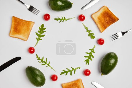 Photo for Top view of toasts, avocados, cherry tomatoes and arugulas leaves, forks and knives on grey background - Royalty Free Image