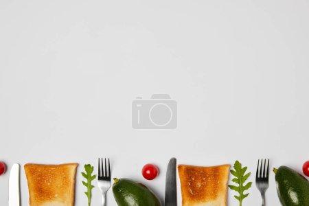 Foto de Vista superior de tostadas, aguacate, tomates cherry, hojas de arugulas, tenedores y cuchillos en fondo gris - Imagen libre de derechos