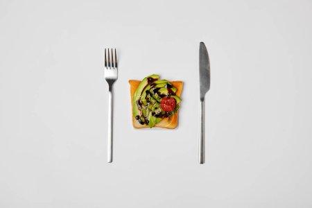 Photo pour Vue de dessus du pain grillé avec avocat et tomate cerise, fourchette et couteau isolé sur gris - image libre de droit
