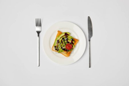 Photo for Top view of toast in plate with avocado and cherry tomato, fork and knive on grey background - Royalty Free Image