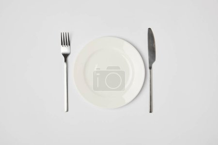 Photo for Top view of porcelain plate with fork and knive on grey background - Royalty Free Image