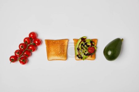 Photo pour Vue de dessus des toasts aux avocats et tomates cerises sur fond gris - image libre de droit