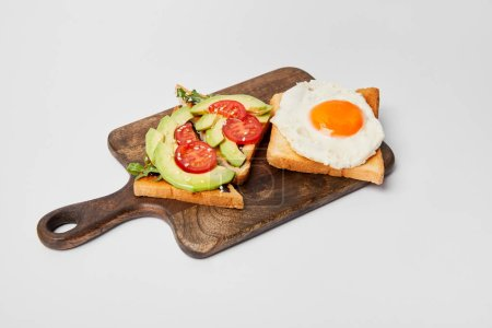 selective focus of wooden cutting board with toasts and scrambled egg on grey background