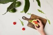 """Постер, картина, фотообои """"вид сверху женская рука тост, деревянная разделочная доска, авокадо и помидорами черри под зеленых растений на поверхности мрамора"""""""
