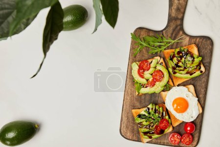 Photo for Top view of wooden cutting board with toasts, scrambled egg, cherry tomatoes and avocados under green plant on marble surface - Royalty Free Image