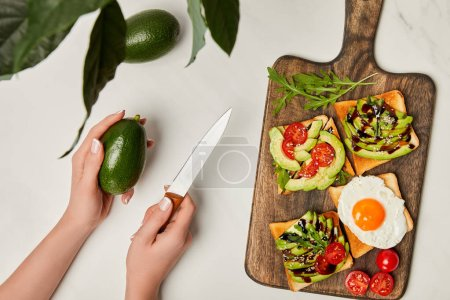 Photo for Top view of womans hands holding knife with avocado and wooden cutting board with toasts on marble surface - Royalty Free Image