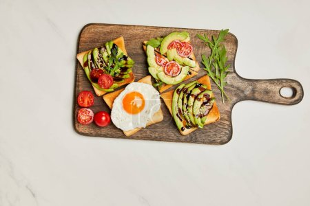 Photo for Top view of wooden cutting board with toasts, scrambled egg and cherry tomatoes on marble surface - Royalty Free Image