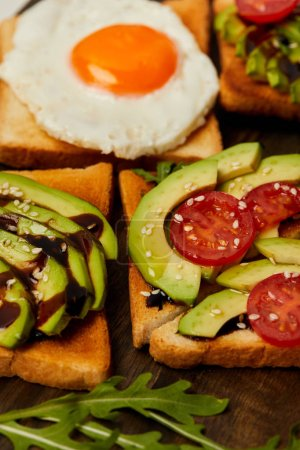 Photo for Selective focus of toasts with scrambled egg, cherry tomato and avocado on wooden background - Royalty Free Image
