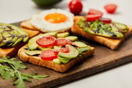 Photo for Selective focus of cutting board with toasts, scrambled egg, cherry tomatoes and avocado on white background - Royalty Free Image