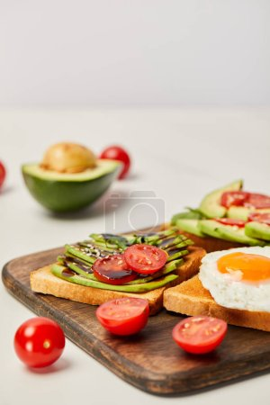 Photo for Selective focus of wooden cutting board with toasts, scrambled egg, cherry tomatoes and avocado on grey background - Royalty Free Image