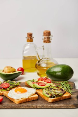 Photo for Selective focus of wooden cutting board with toasts, scrambled egg, cherry tomatoes, avocados and oil bottles on grey background - Royalty Free Image