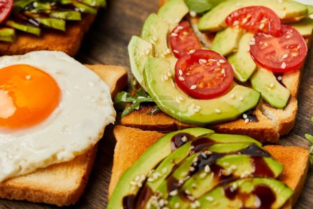 Photo for Selective focus of toasts with scrambled egg, cherry tomatoes and avocado on wooden background - Royalty Free Image