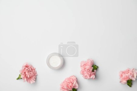 Photo for Top view of pink carnations flowers and cream container on white background - Royalty Free Image