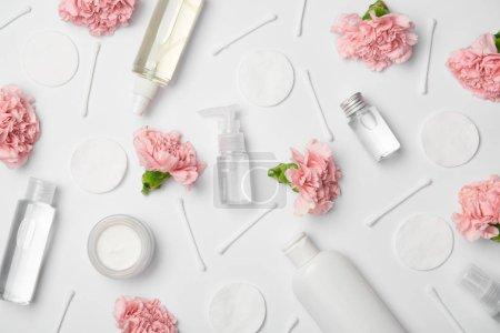 Photo pour Vue du dessus de différentes bouteilles cosmétiques, fleurs d'oeillets, bâtons de coton et tampons cosmétiques sur fond blanc - image libre de droit