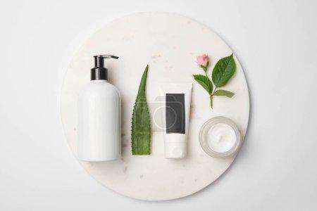 Photo pour Vue de dessus de différents récipients cosmétiques, feuille d'aloe vera et fleur de rose sur surface ronde blanche - image libre de droit