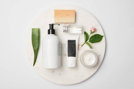 Photo for Top view of different cosmetic containers, soap, aloe vera leaf and rose flower on white round surface - Royalty Free Image