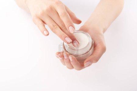 Photo pour Vue partielle de la femme appliquant de la crème pour les mains sur fond blanc - image libre de droit