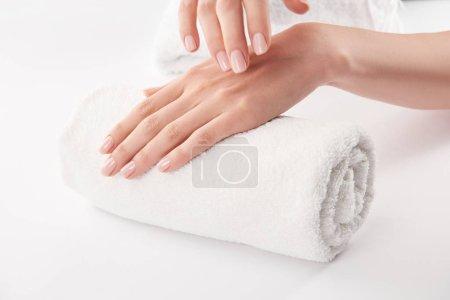 Photo pour Vue partielle des mains féminines sur une serviette éponge sur fond blanc - image libre de droit