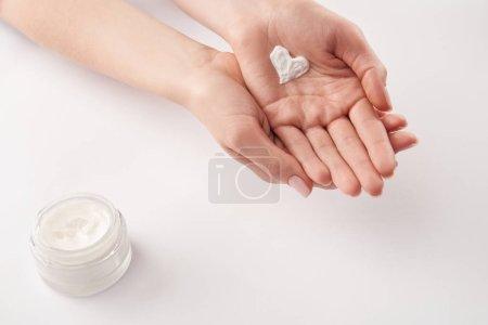 Photo pour Vue partielle de la femme appliquant la crème cosmétique en forme de coeur sur fond blanc - image libre de droit