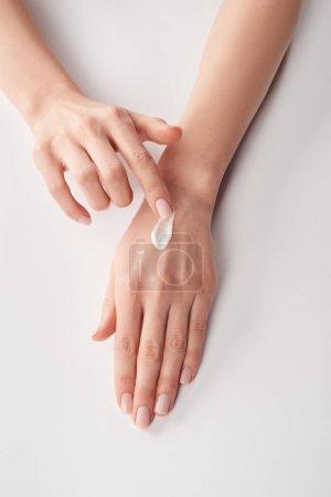 Photo pour Vue partielle de la femme appliquant la crème cosmétique sur fond blanc - image libre de droit