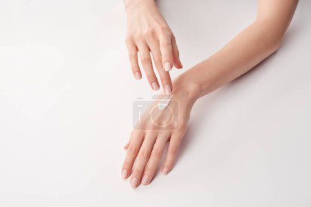Photo for Partial view of woman applying cosmetic cream on white background - Royalty Free Image