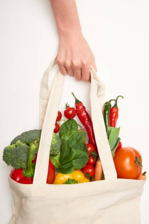 Photo for Cropped view of woman holding eco bag with vegetables on white background - Royalty Free Image