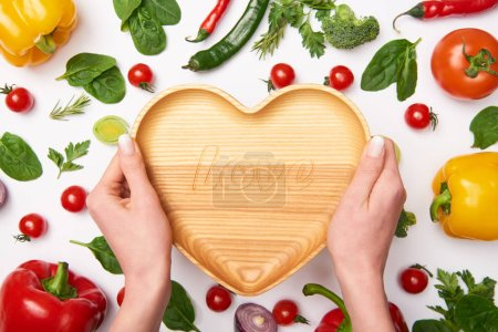 Photo for Partial view of woman holding wooden cutting board and vegetables on white background - Royalty Free Image