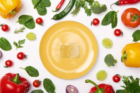Photo for Flat lay with yellow plate and vegetables on white background - Royalty Free Image