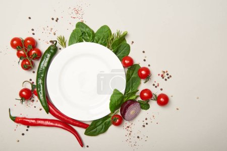 Foto de Vista superior de la placa blanca, verduras y especias en fondo gris - Imagen libre de derechos