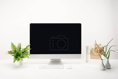 Foto de Lugar de trabajo con las plantas verdes y computadora de escritorio con copia espacio, aislada sobre fondo blanco - Imagen libre de derechos