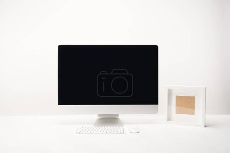 Photo for Workplace with photo frame and desktop computer with copy space isolated on white - Royalty Free Image
