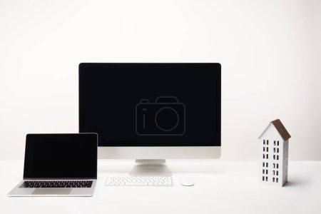 Foto de Lugar de trabajo con el modelo de la casa, computadora de escritorio y laptop con copia espacio, aislada sobre fondo blanco - Imagen libre de derechos