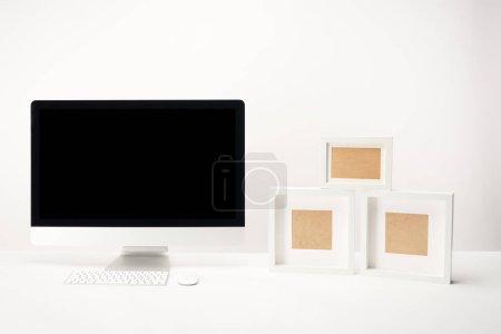 Photo pour Lieu de travail avec les cadres photo et ordinateur de bureau avec espace copie isolé sur blanc - image libre de droit