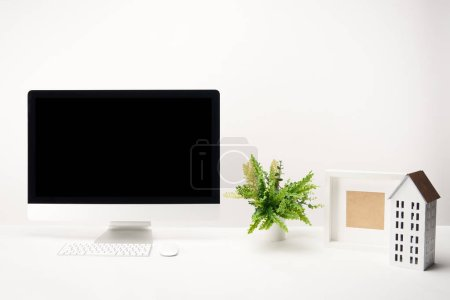 Foto de Trabajo con plantas, la casa modelo, foto marco y computadora de escritorio con copia espacio, aislada sobre fondo blanco - Imagen libre de derechos