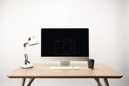 workplace with lamp, coffee to go and desktop computer with copy space isolated on white