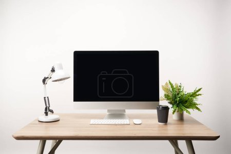 Photo for Workplace with coffee to go, lamp, green plant and desktop computer with copy space isolated on white - Royalty Free Image
