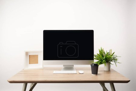 Photo for Workplace with coffee to go, photo frame, green plant and desktop computer with copy space isolated on white - Royalty Free Image