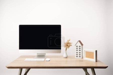 Photo for Workplace with house model, dry flowers and desktop computer with copy space isolated on white - Royalty Free Image
