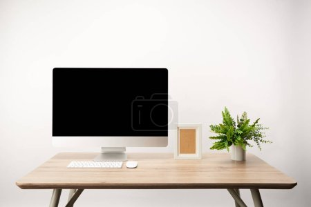 Photo for Workplace with green plant, photo frame and desktop computer with copy space isolated on white - Royalty Free Image