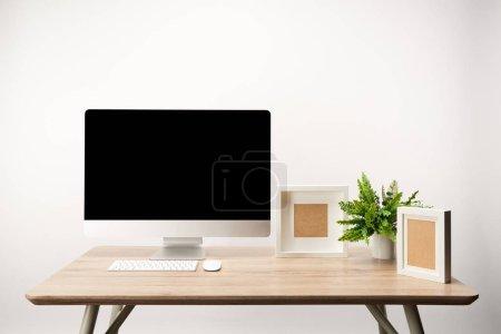 Photo pour Lieu de travail avec photo frames, vert plante et ordinateur de bureau ordinateur avec copie espace isolé sur blanc - image libre de droit