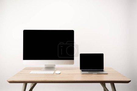 Foto de Lugar de trabajo con ordenador de sobremesa y portátiles con espacio de copia en mesa de madera aislado en blanco - Imagen libre de derechos
