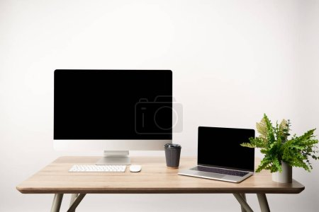 Photo for Workplace with desktop computer and laptop with copy space on wooden table isolated on white - Royalty Free Image