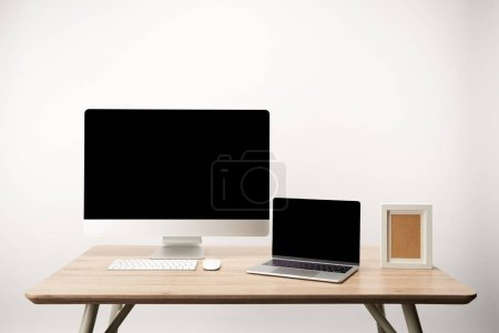 Photo for Workplace with photo frame, desktop computer and laptop with copy space on wooden table isolated on white - Royalty Free Image