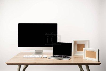 Photo pour Lieu de travail avec des cadres photo, ordinateur de bureau et portable avec espace copie sur table en bois isolé sur blanc - image libre de droit
