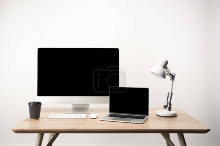 Photo for Workplace with lamp, coffee to go, desktop computer and laptop with copy space isolated on white - Royalty Free Image