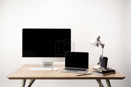 Photo pour Lieu de travail avec lampe, café aller, ordinateurs portables, ordinateur de bureau et portable avec copie espace isolé sur blanc - image libre de droit