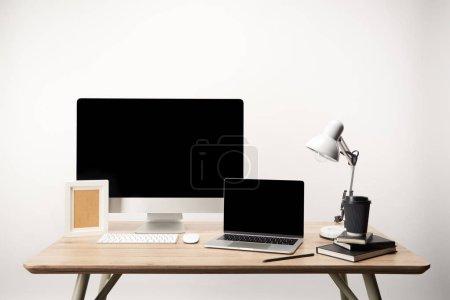 Photo pour Lieu de travail avec cadre photo, café aller, ordinateurs portables, ordinateur de bureau et portable avec copie espace isolé sur blanc - image libre de droit