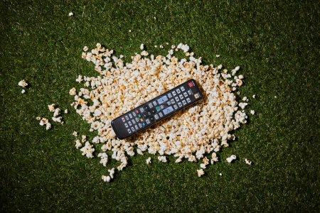 Photo pour Vue du dessus du maïs soufflé situé près de la télécommande sur l'herbe verte - image libre de droit