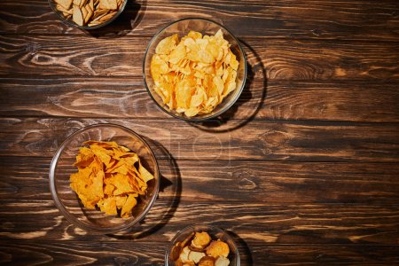 top view of party snacks in bows on wooden table