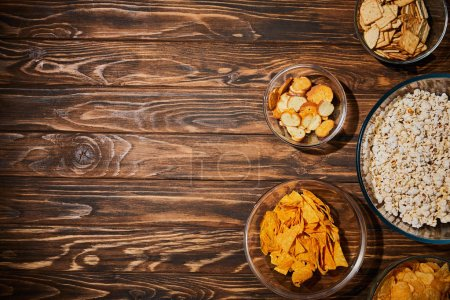 top view of snacks in bows on wooden table